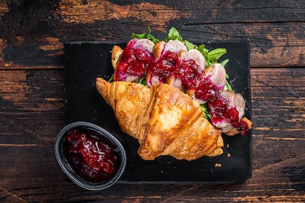 Panino con fettine di filetto di petto d'anatra, rucola e salsa. tavolo in legno scuro. vista dall'alto.