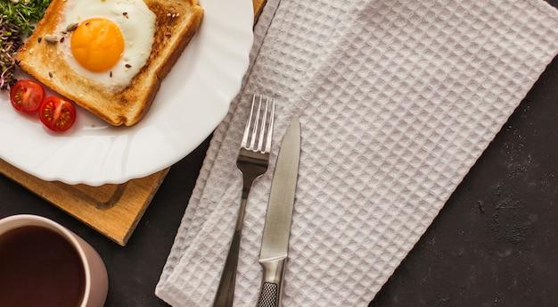 Un panino con l'uovo nel foro del pane, i microgreens, una tazza di tè e un cibo sano prima colazione