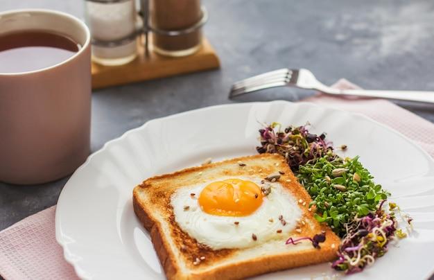 Un panino con l'uovo nel foro del pane, microgreens, cibo sano colazione, una tazza di tè