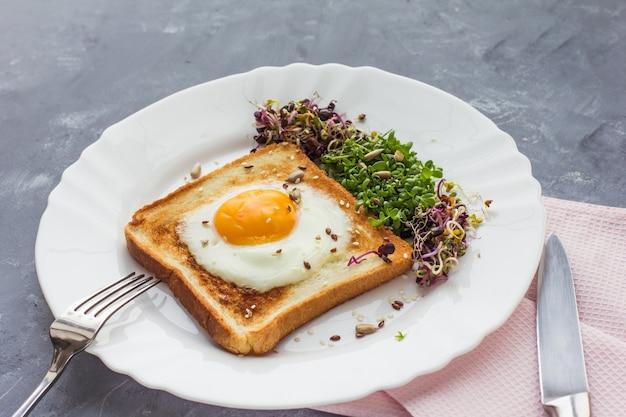 Un panino con l'uovo nel foro del pane, microgreens, cibo sano colazione, sfondo grigio