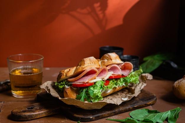 Panino con prosciutto formaggio pomodoro e lattuga su fondo scuro