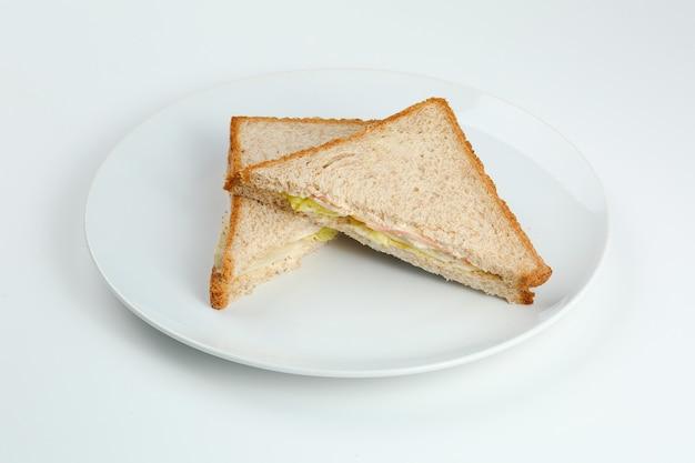 Panino con prosciutto e insalata su pane tostato integrale in piastra bianca. club sandwich isolato