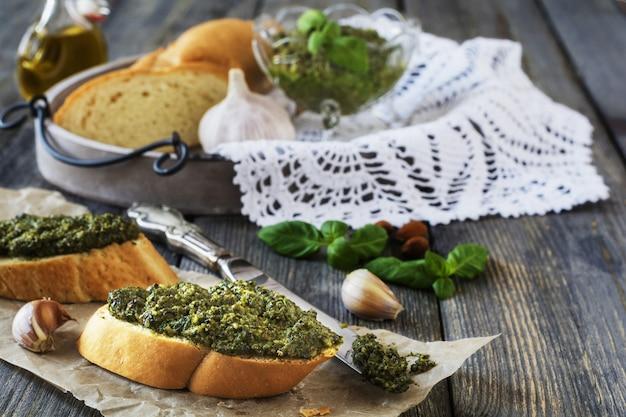 Panino con pesto fatto in casa, basilico, olio d'oliva e aglio su un vecchio fondo di tavola in legno. messa a fuoco selettiva.