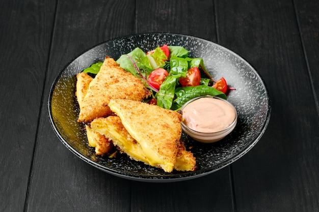 Panino con cheddar fuso e insalata su un piatto