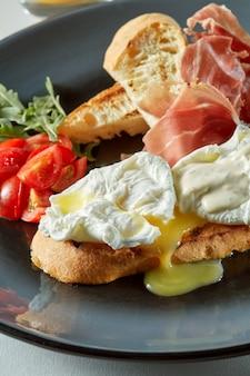 Panino con uovo in camicia, prosciutto di parma e pomodoro su un piatto