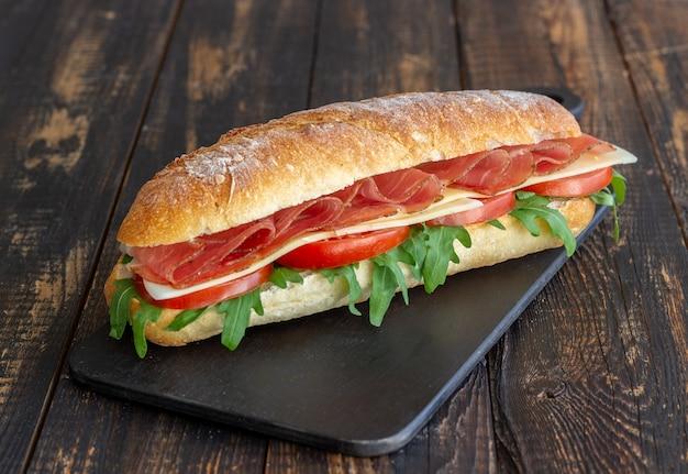 Panino con prosciutto, pomodori, rucola e formaggio. mangiare sano. dieta.