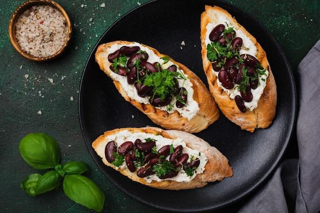 Panino con fagioli rossi, aglio, olio d'oliva e ricotta su superficie scura