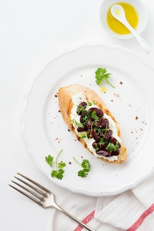 Panino con fagioli rossi, aglio, olio d'oliva e ricotta sulla superficie bianca