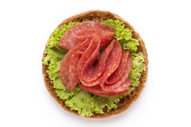 Panino con salame su sfondo bianco.