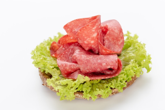 Panino con salame salsiccia su sfondo bianco.