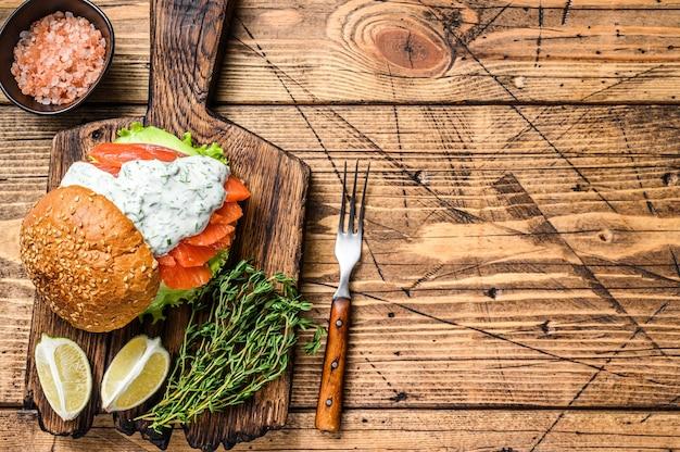 Panino con pesce salato, salmone, avocado, panino con hamburger, salsa di senape e insalata iceberg. fondo in legno. vista dall'alto. copia spazio.