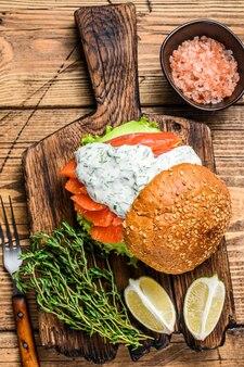 Panino con salmone salato, avocado, panino con hamburger, salsa di senape e insalata iceberg