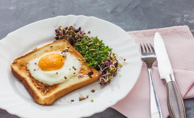 Panino con uova strapazzate, pomodori, germogli di rucola e ravanelli, micro-verdure cibo sano