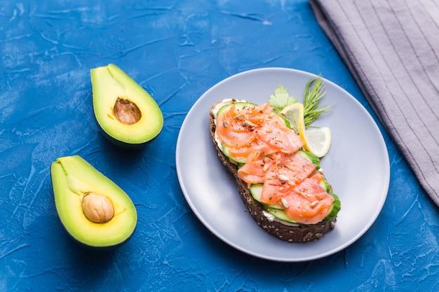 Panino con salmone affumicato e cetriolo su sfondo blu con avocado, vista dall'alto. concetto per