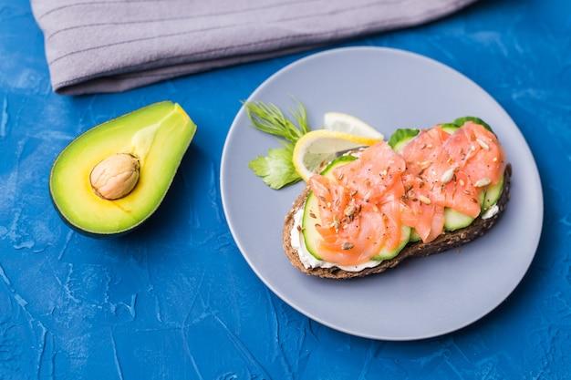 Panino con salmone affumicato e cetriolo sulla superficie blu con avocado, vista dall'alto. concetto per una sana alimentazione.