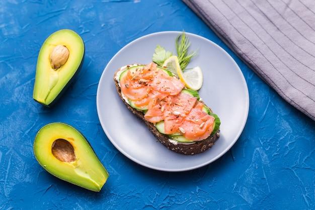 Panino con salmone affumicato e cetriolo sulla parete blu con avocado, vista dall'alto. concetto per una sana alimentazione.
