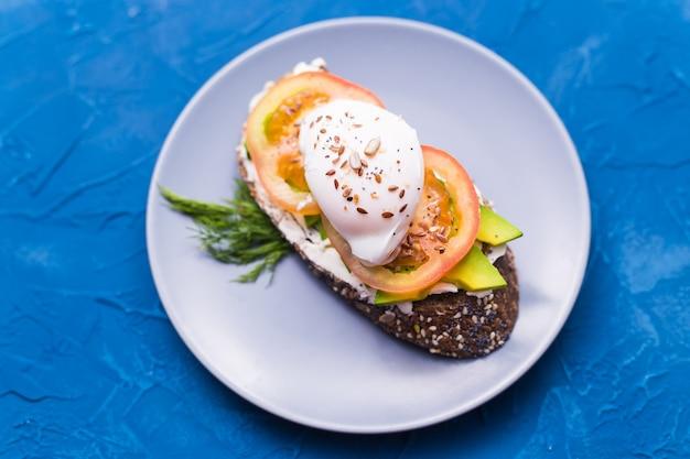 Panino con salmone affumicato, uova e avocado su sfondo blu, vista dall'alto. concetto per un sano