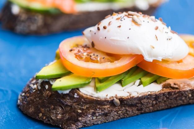 Panino con salmone affumicato, uova e avocado sulla superficie blu. concetto per una sana alimentazione.