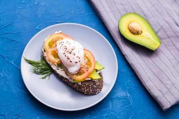 Panino con salmone affumicato, uova e avocado su superficie blu, vista dall'alto. concetto per una sana alimentazione.