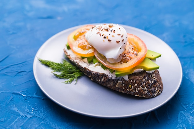 Panino con salmone affumicato, uova e avocado su superficie blu, vista dall'alto. concetto per un sano