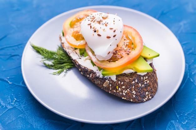 Panino con salmone affumicato, uova e avocado sul blu