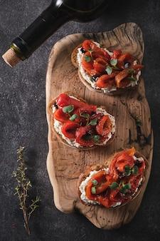 Panino con formaggio a pasta molle e peperone rosso al forno su una tavola di legno. antipasti italiani di bruschetta
