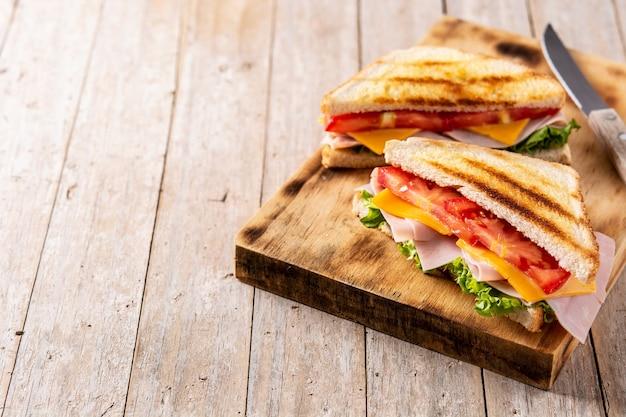 Panino con pomodoro, lattuga, prosciutto e formaggio su tavola di legno