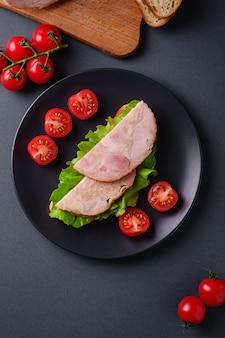 Panino con carne di prosciutto di tacchino, insalata verde e fette di pomodorini freschi sulla banda nera vicino agli ingredienti sul tagliere
