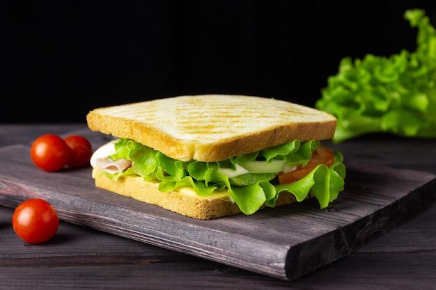 Panino con pane bianco, lattuga e verdure su uno sfondo scuro. uno spuntino veloce e salutare.