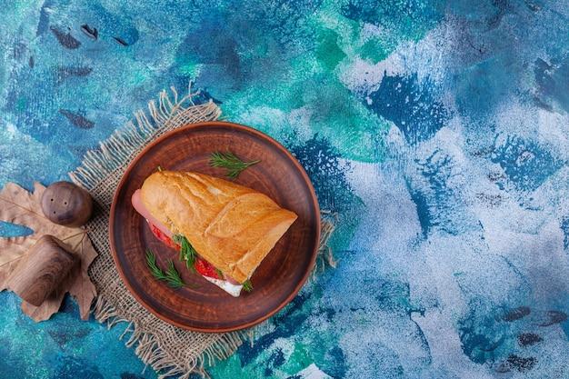 Panino su un piatto di legno sul tovagliolo di tela da imballaggio, sul blu.