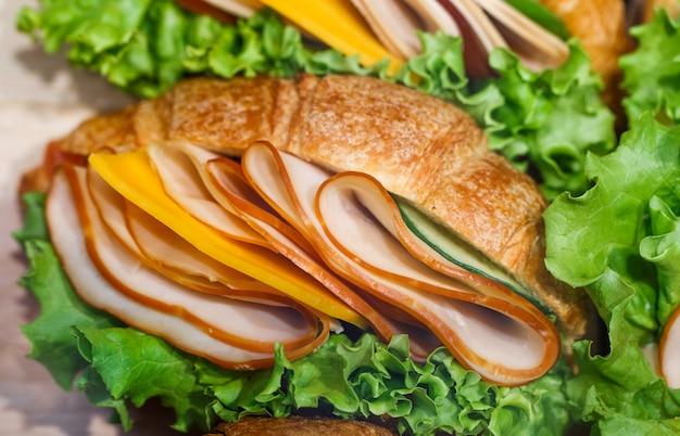 Croissant di tramezzini con prosciutto cotto a fette e insalata verde