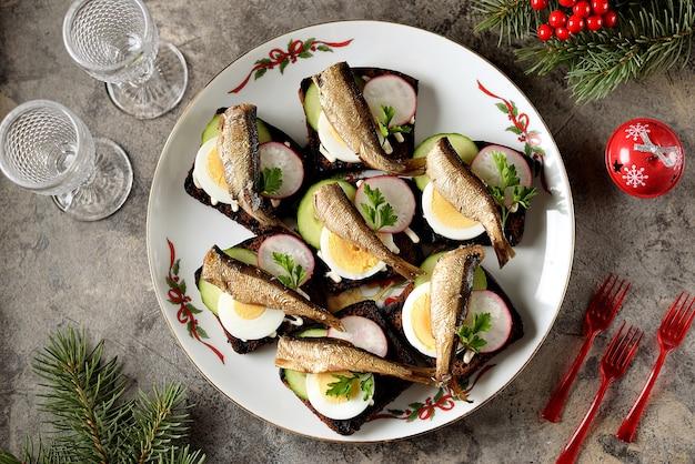 Panini di spratto baltico su pane di segale con ravanelli di cetriolo e uova