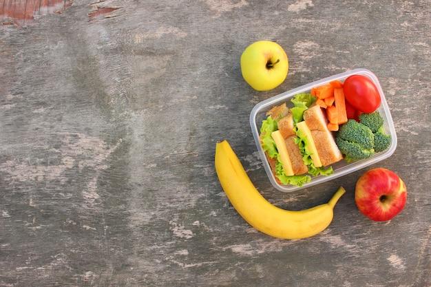 Panini, frutta e verdura in scatola per alimenti su fondo di legno vecchio. vista dall'alto. disposizione piatta.
