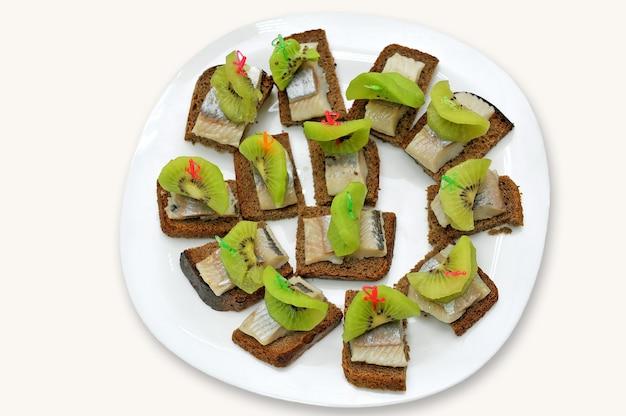 Panini di pane nero, fette di filetto di aringhe marinate e kiwi sulla piastra, isolato su uno sfondo bianco.