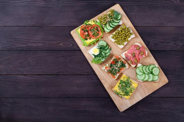 Panini su pane tostato con crema di formaggio con salmone, germogli, verdure giacciono su una tavola di legno
