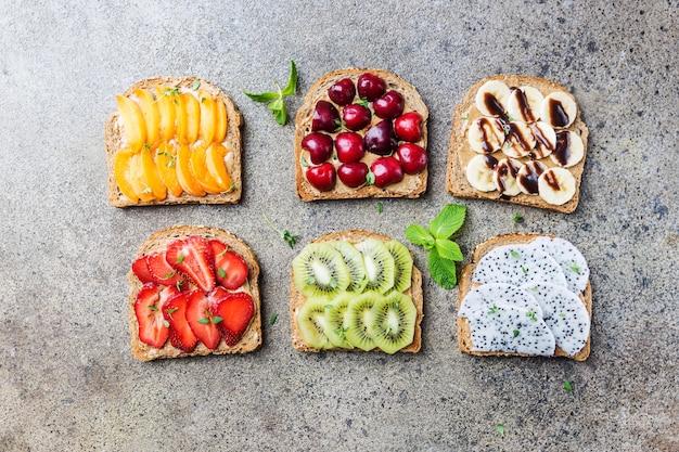 Panini di pane tostato con burro di arachidi, frutti di bosco e frutta pesca, fragola, banana, ciliegia, kiwi e frutta del drago