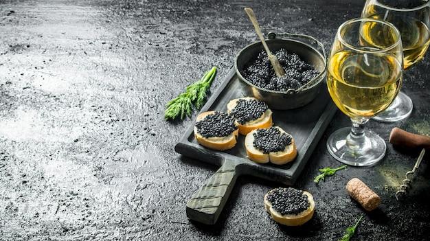 Panini con caviale nero, caviale in una ciotola e vino bianco. su sfondo nero rustico