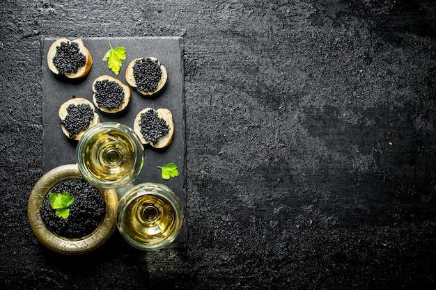Panini con caviale nero e caviale in una ciotola con vino in bicchieri. sul nero rustico