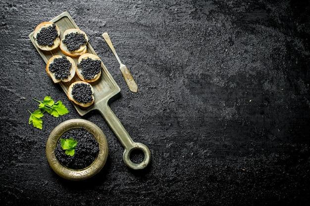 Panini con caviale nero sul tagliere. su sfondo nero rustico