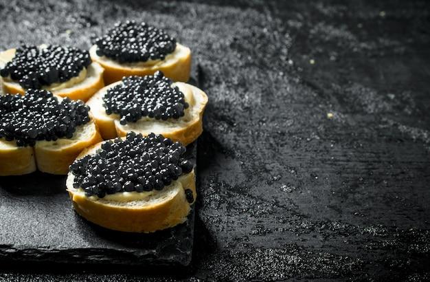 Panini con caviale nero su una tavola di pietra. sul nero rustico