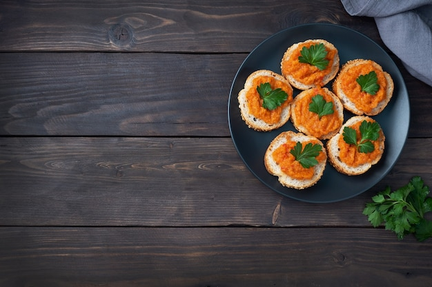 Panini con pane zucchine caviale pomodori cipolle. cibo vegetariano fatto in casa. verdura stufata in scatola. sfondo in legno vista dall'alto, copia spazio