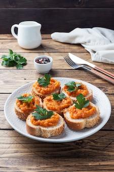 Panini con pane zucchine caviale pomodori cipolle. cibo vegetariano fatto in casa. verdura stufata in scatola. superficie in legno