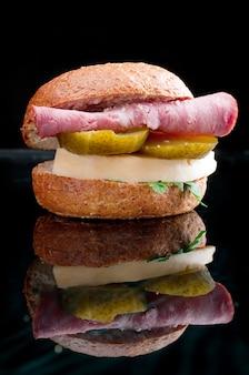Panini con formaggio e prosciutto, cetriolo con la riflessione