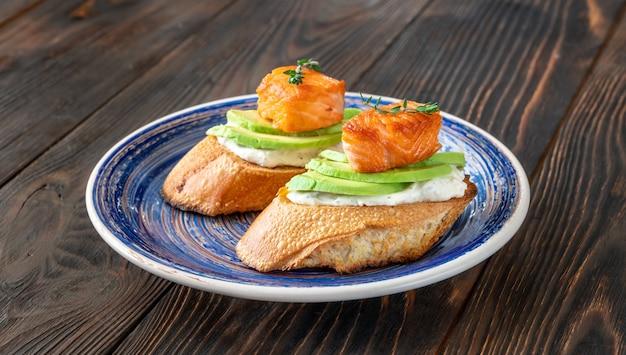 Panini con crema di formaggio, avocado fresco e salmone fritto