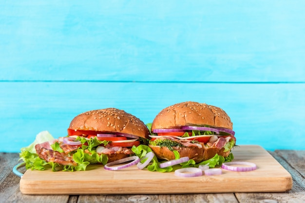 Panini con lattuga, pancetta, anelli di cipolla, pomodori, uova, formaggio e panino al sesamo su sfondo azzurro.