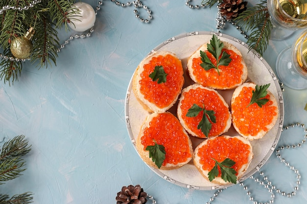 I panini con caviale rosso si trovano su un piatto su uno sfondo azzurro