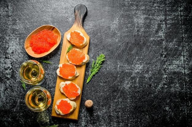 Panini con caviale rosso, caviale in una ciotola e vino in bicchieri. sulla tavola rustica nera