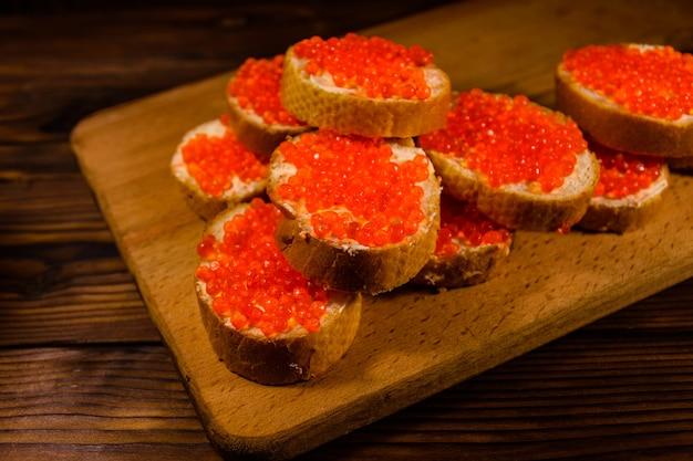Panini con caviale rosso su tagliere