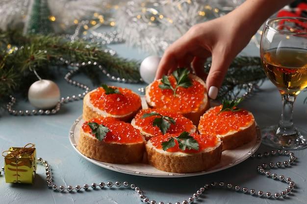 Panini con caviale rosso su un piatto contro uno sfondo azzurro. spuntino festivo. la donna allunga la mano per togliere il panino dal piatto.