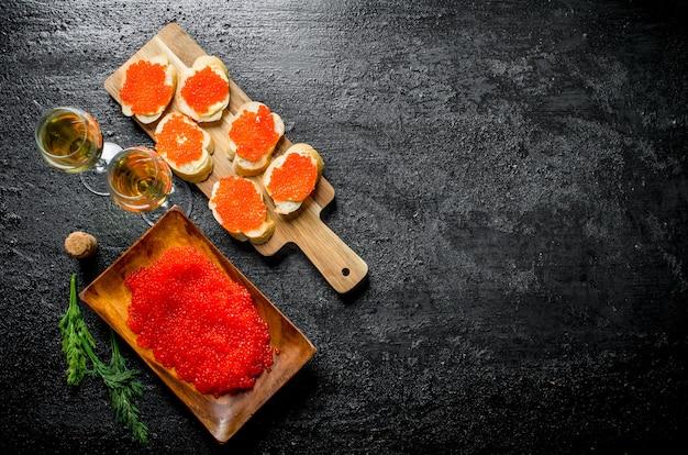 Panini con caviale rosso e caviale rosso su un piatto con il vino. sul nero rustico